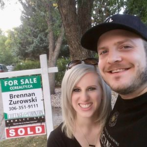 Tyler and Victoria Carlson by house sold sign